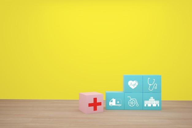 Hand, die den blauen würfelblock stapelt mit dem ikonengesundheitswesen medizinisch vereinbart.