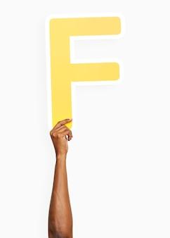 Hand, die den buchstaben f hält