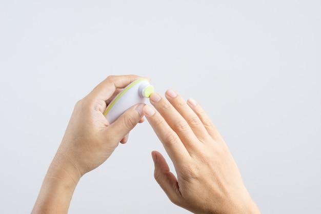 Hand, die den fingernagelschneider poliert oder ausrüstung für kind, selbstmaniküreprozeß poliert