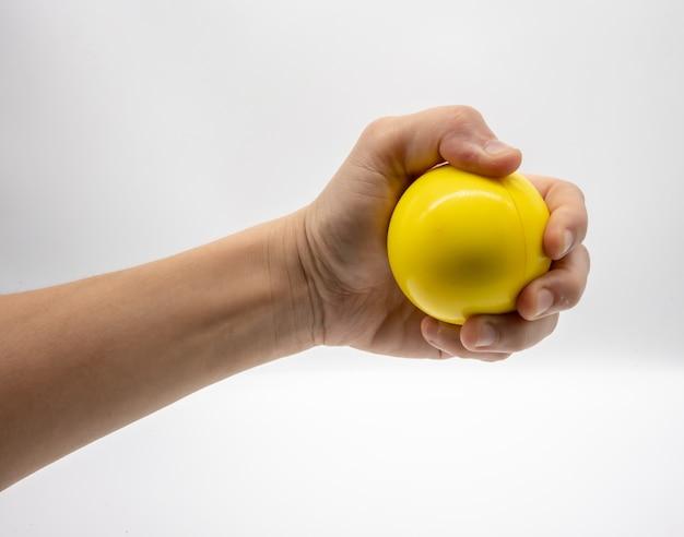 Hand, die den gelben druckball lokalisiert auf weiß hält