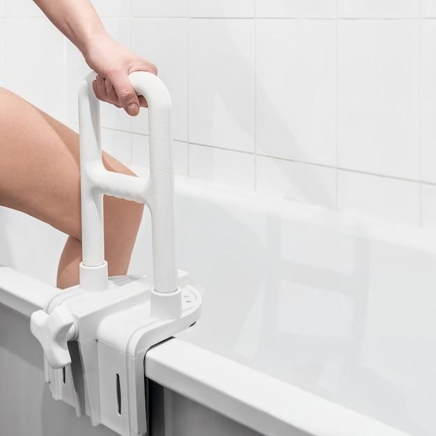 Hand, die den handlauf im badezimmer hält