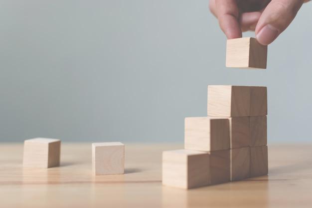 Hand, die den hölzernen block stapelt als stufentreppe vereinbart. leiter karriereweg