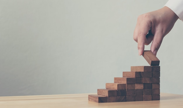 Hand, die den hölzernen block stapelt als stufentreppe vereinbart. leiterkarriere-wegkonzept für geschäftswachstums-erfolgsprozeß, kopienraum