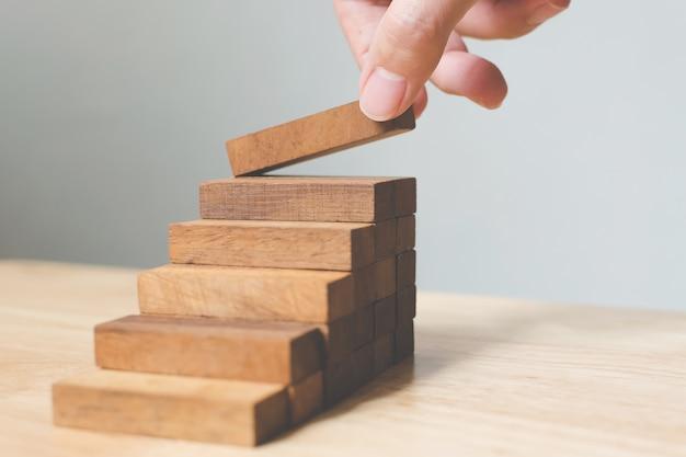 Hand, die den hölzernen block stapelt als stufentreppe vereinbart.