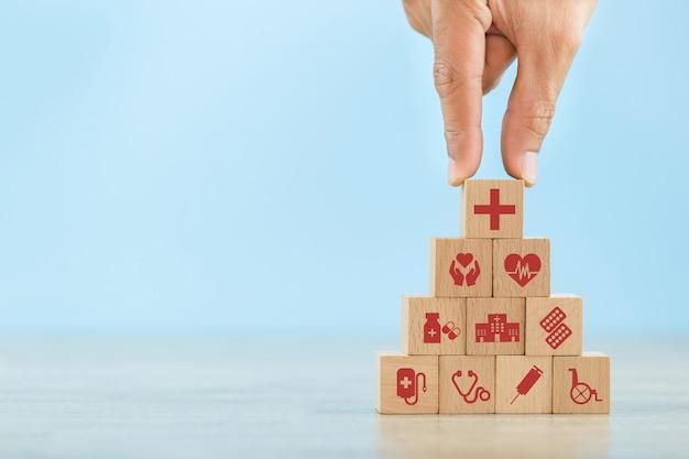 Hand, die den hölzernen block stapelt mit dem medizinischen ikonengesundheitswesen anordnet.