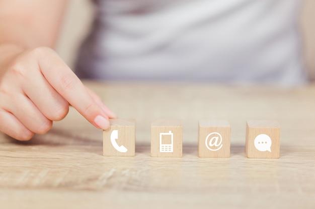 Hand, die den hölzernen block stapelt mit iconl telefon, post, adresse und handy vereinbart