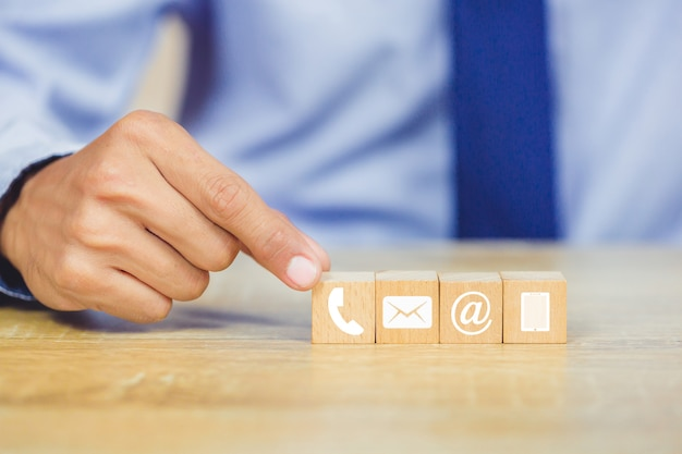 Hand, die den hölzernen block stapelt mit ikonentelefon, -post, -adresse und -handy vereinbart