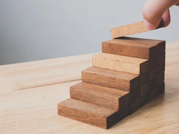 Hand, die den hölzernen blockstapeln als schritttreppe vereinbart