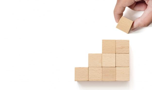 Hand, die den holzklotz stapelt als stufentreppe vereinbart. geschäftskonzept für wachstumserfolgsprozess. kopieren sie platz