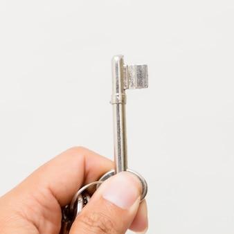 Hand, die den schlüssel lokalisiert auf weiß hält