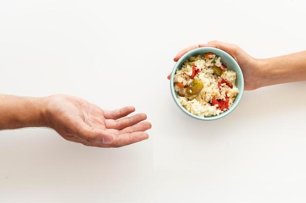 Hand, die der bedürftigen person eine fressnapf gibt