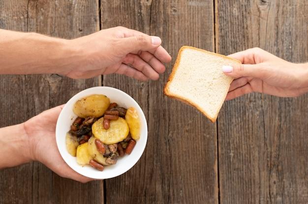 Hand, die der bedürftigen person eine schüssel mit essen und brot gibt