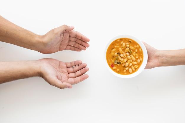 Hand, die der bedürftigen person suppenschüssel gibt