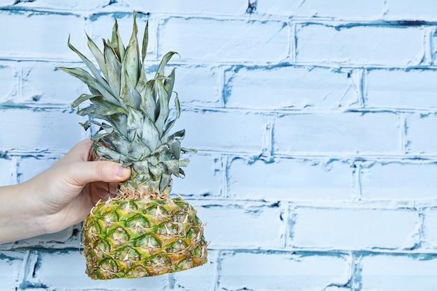 Hand, die die hälfte der ananas hält.