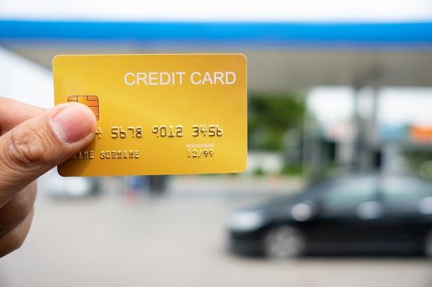 Hand, die die kreditkarte in der tankstelle hält