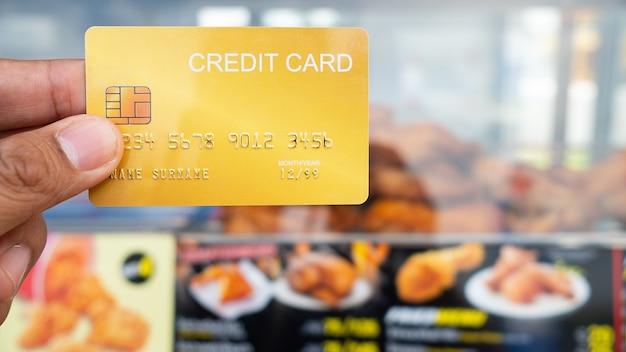 Hand, die die kreditkarte mit gebratenem hühnerladen hält