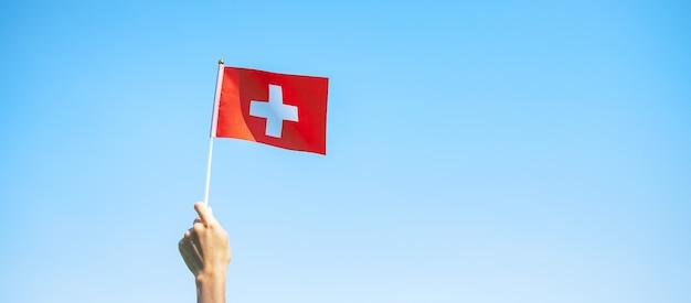 Hand, die die schweiz-flagge auf hintergrund des blauen himmels hält. schweizer nationalfeiertag und fröhliche feierkonzepte