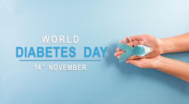 Hand, die die symbolische bogenfarbe des blauen bandes hält, die das bewusstsein am diabetestag weckt