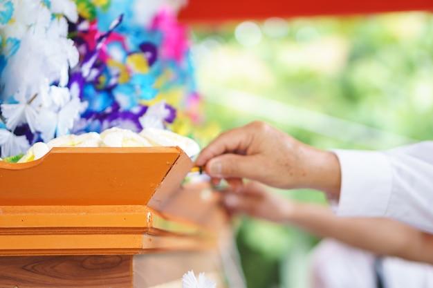 Hand, die die thailändische künstliche begräbnis- blume verwendet für kremationsritus gibt