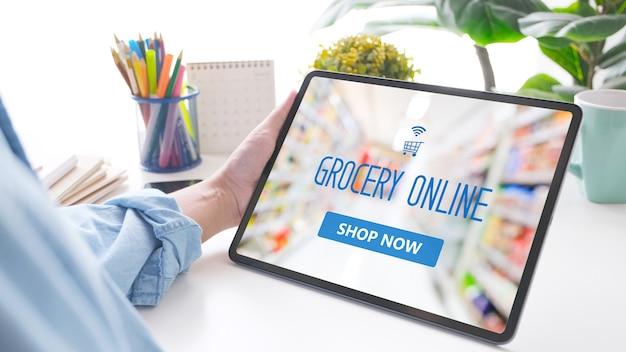 Hand, die digitale tablette mit lebensmittel-online-shopping-anwendung auf dem gerätebildschirm über unscharfem supermarkthintergrund, geschäft und technologie, lifestyle-konzept hält