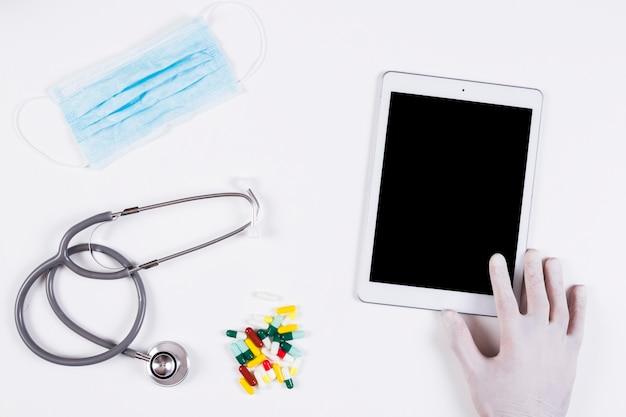 Hand, die digitale tablette mit maske hält; stethoskop und bunte kapseln auf weißem hintergrund