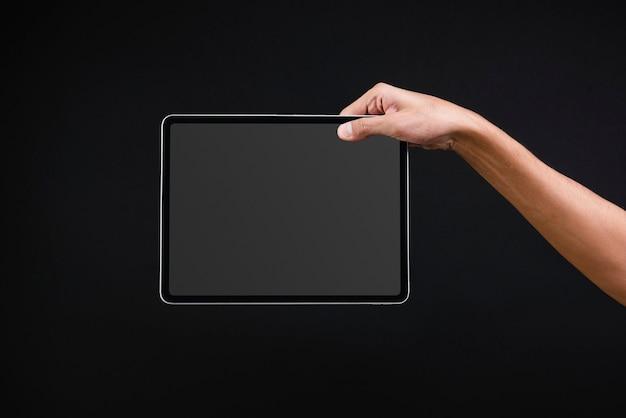 Hand, die digitales tablett mit leerem schwarzen bildschirm hält