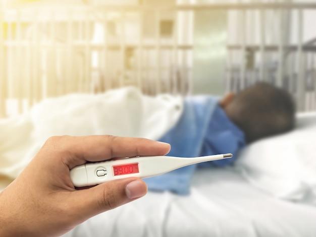 Hand, die digitales thermometer mit hohem fieber über verschwommenes krankes asiatisches kind mit blauer patiententuchuniform hält, die auf krankenhausbett schläft. gesundheitswesen und medizinisches konzept.