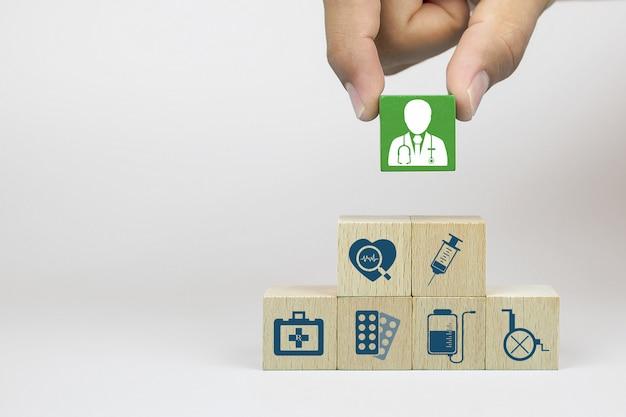 Hand, die doktorikone auf würfelholzspielzeugblöcken mit gestapelten medizinischen symbolen aufnimmt.