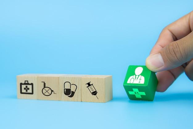 Hand, die doktorikone auf würfelholzspielzeugblöcken mit medizinischen symbolen aufnimmt. konzepte der krankheitsbehandlung und krankenversicherung.