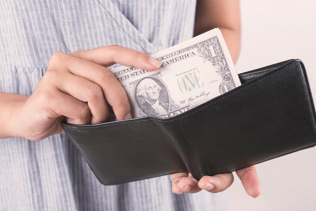 Hand, die dollargeld mit geldbörse auf weißem hintergrund hält.