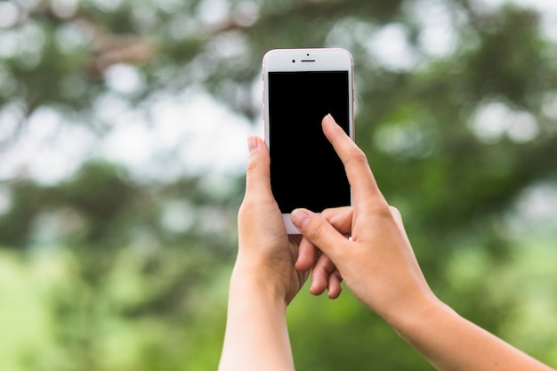 Hand, die draußen den schirm von mobile berührt