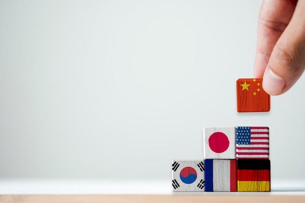Hand, die druckschirm china-flagge auf die oberseite der internationalen flagge setzt. es ist mehr als andere länder der welt ein symbol für das wirtschaftswachstum chinas. - wirtschaftskonzept.