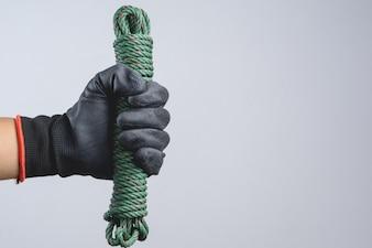 Hand, die dunklen Handschuh trägt und grüne Fallschirmschnur des Nylonseils als Entführer hält