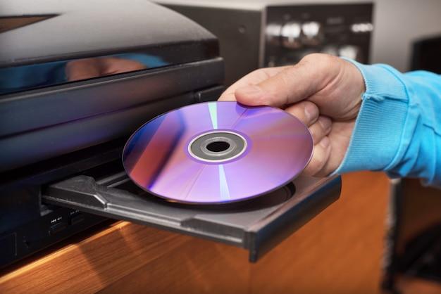 Hand, die dvd hält, die zum videoplayer einfügt