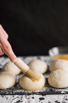 Hand, die eigelb über den ungekochten brötchen anwendet