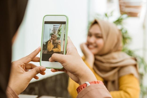 Hand, die ein bild eines verschleierten mädchens macht, das mit einem smartphone lächelt