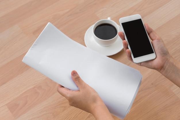 Hand, die ein blatt papier, ein handy und einen kaffee auf dem tisch