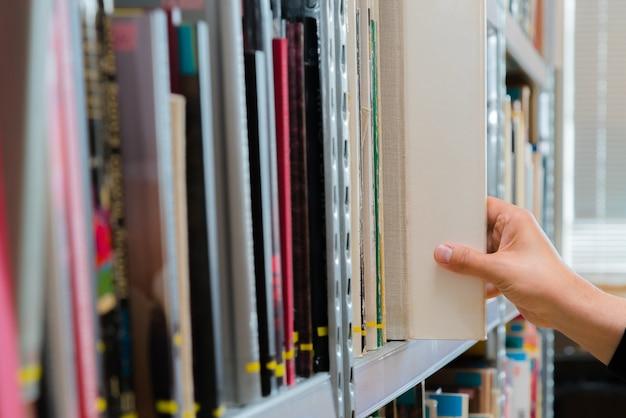 Hand, die ein buch aus dem regal in der bibliothek auswählt.