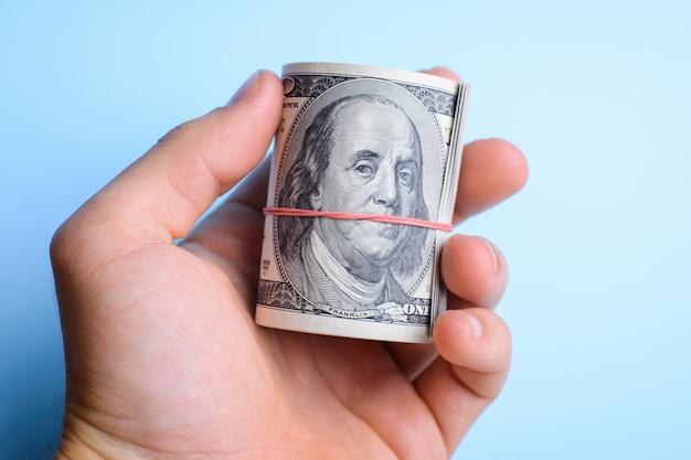 Hand, die ein bündel dollar bargeld über einem blauen hintergrund hält