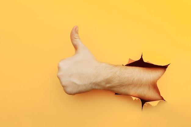 Hand, die ein daumen hoch zeichen durch ein zerrissenes loch in der gelben papierwand gut gemachtes gutes jobkonzept zeigt