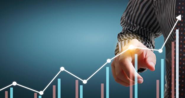 Hand, die ein diagramm des finanzindikators und des diagramms der marktwirtschaftsanalyse des rechnungswesens berührt