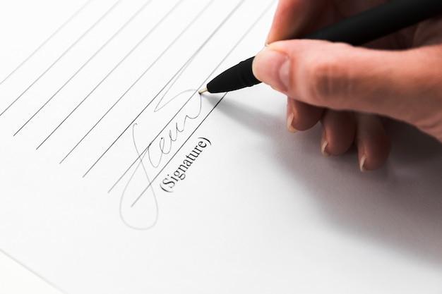 Hand, die ein dokument mit einem stift unterzeichnet