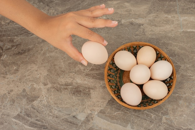 Hand, die ein ei und einen korb der weißen eier nimmt.