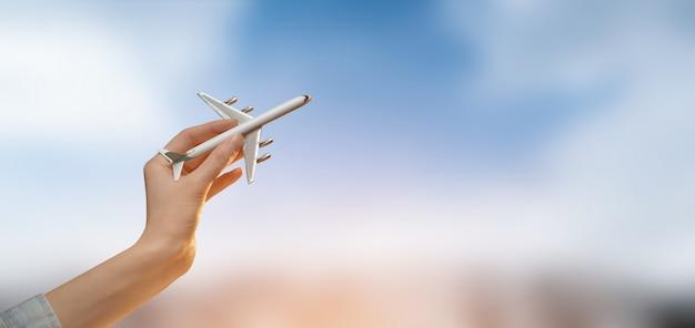 Hand, die ein flugzeug über unscharfer stadt mit himmel hält. tourismus oder reise