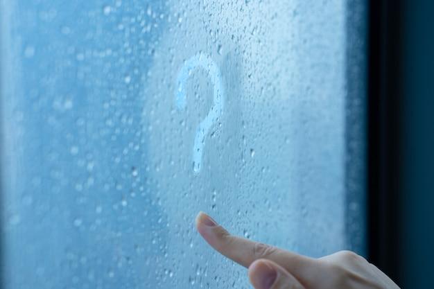 Hand, die ein fragezeichen auf einem nebligen fenster während des regens zeichnet