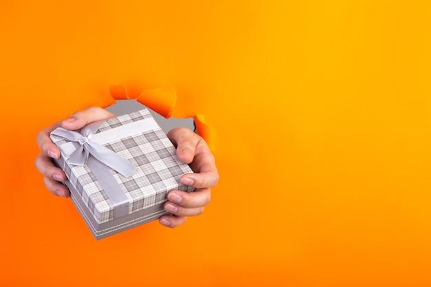 Hand, die ein geschenk durch ein orange zerrissenes papier hält