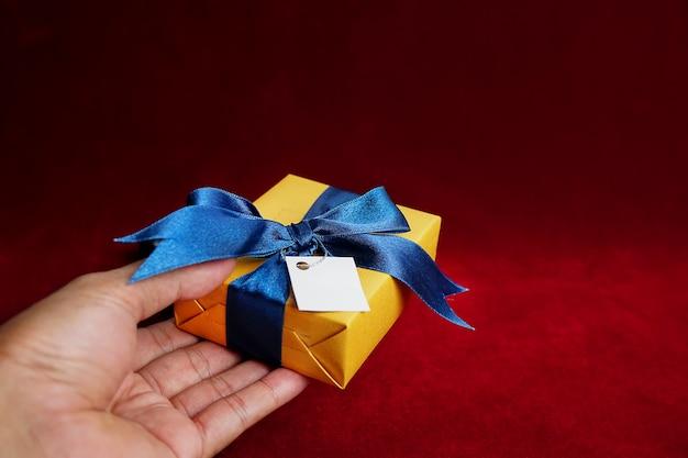 Hand, die ein geschenk mit einem blauen band auf rotem hintergrund hält hände und geschenkbox