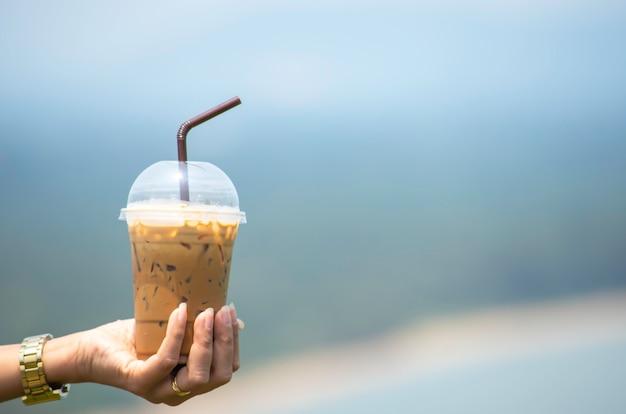 Hand, die ein glas des kalten espressokaffees hält hintergrund verschwommen blickt ansichten baum und wasser.