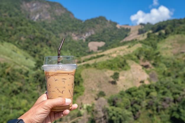 Hand, die ein glas kalten espressokaffee hält hintergrund verschwommene ansichten baum und berg