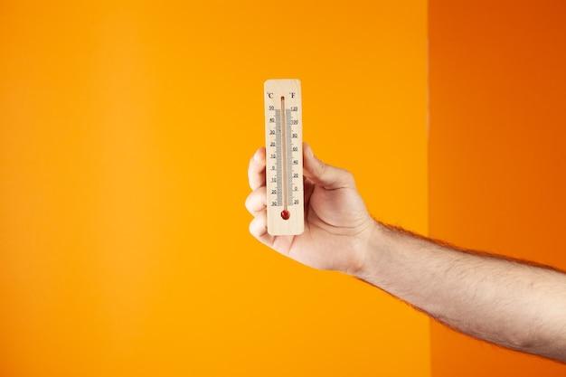 Hand, die ein hausthermometer hält. lufttemperatur auf orangem hintergrund